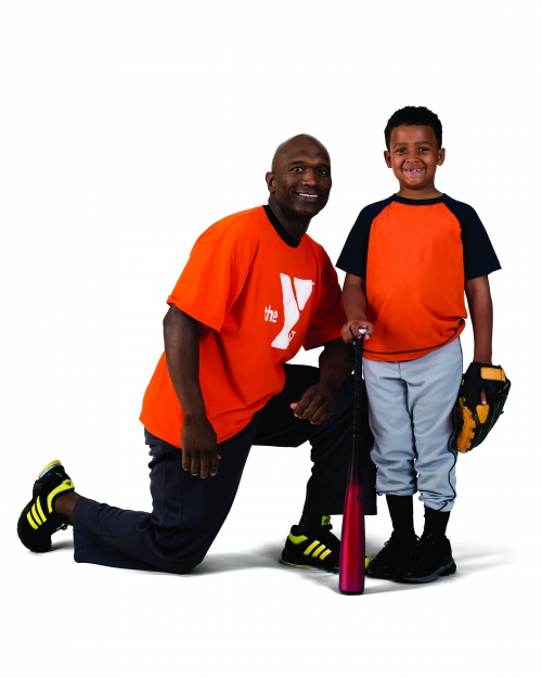Volunteer with a child holding baseball gear