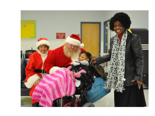 Santa and Mrs. Claus standing with a Special Populations Participant and family